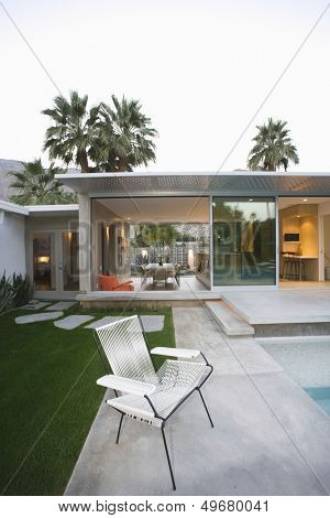 Empty chair on paved poolside area of a home