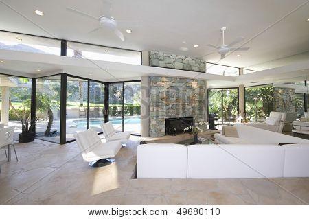 Afundado, área de estar e lareira de pedra exposta na sala de estar espaçosa com vista piscina um