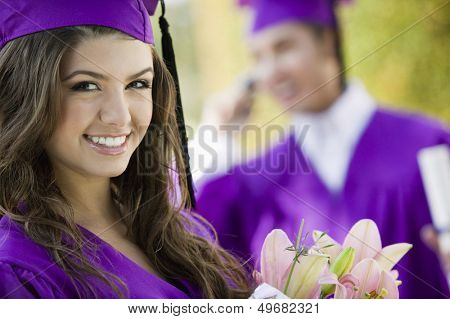 Portrait of beautiful graduate student with flower bouquet