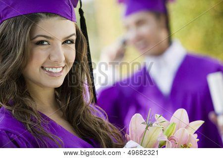 Portrait of beautiful graduate student with flower bouquet