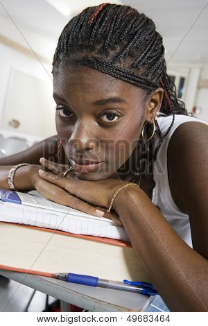Closeup portrait of bored young African American student resting on stack of books in classroom