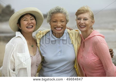 Portrait of cheerful female friends enjoying vacation at beach