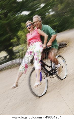 Full length of excited man riding bicycle while woman sitting on handlebar