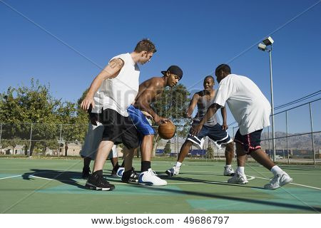 Full length of young men playing basketball on court