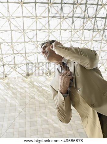 Low angle view of businessman using mobile phone under ceiling