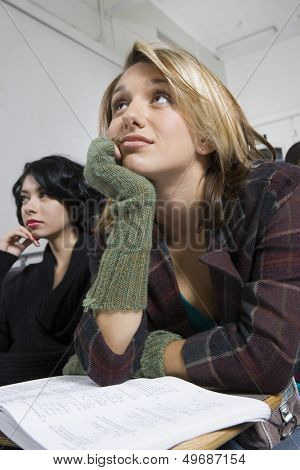 Young female college students listening in classroom