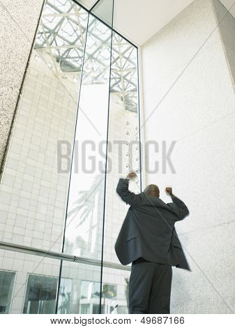 Low angle rear view of an African American businessman celebrating victory in office building