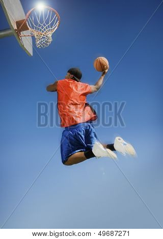 Low angle view of man dunking basketball into hoop against clear blue sky