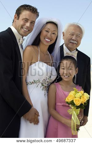 Portrait of happy bride and groom with guests standing against sky