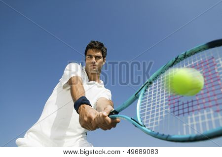 Low angle view of determined young man playing tennis against blue sky