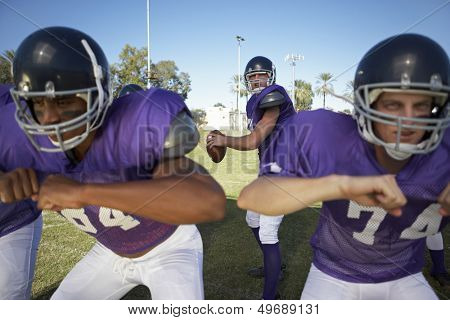 Young men playing American football on field