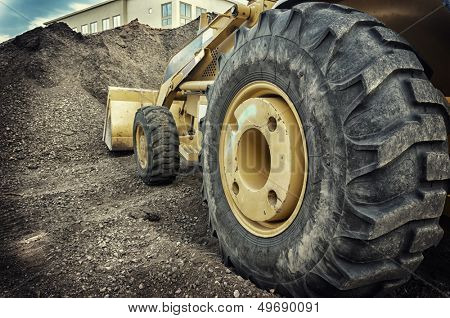 Bull dozer heavy duty construction site focus on large tire.