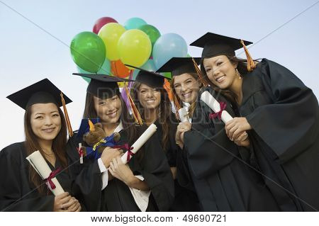Portrait of happy female students with diplomas and balloons standing against sky