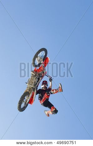 Low angle view of motocross racer performing stunt in midair against clear blue sky