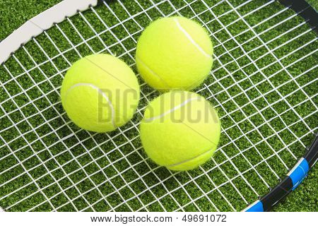 Three Tennis Balls Lie On A Tennis Racket Strings. Over Green Lawn Surface. Tennis Concept