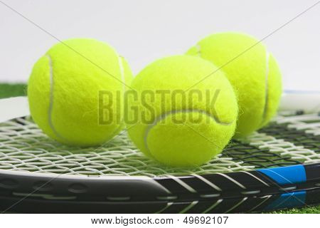 Tennis Concept: Extreme Closeup, Tennis Racket With Balls Lies On Green Grass Court