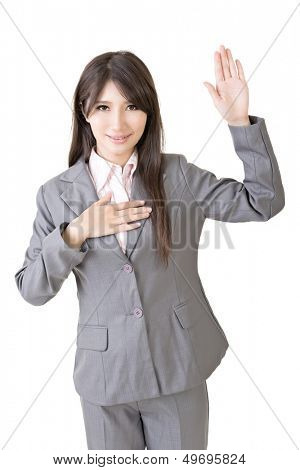Asian business woman give you a gesture of swear. Isolated on the white background.
