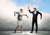 stock photo of rope pulling  - Image of businesspeople hanging on strings like marionettes - JPG