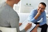 stock photo of psychology  - Female psychologist consulting mature man during psychological therapy session - JPG