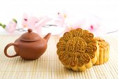 Chinese mid autumn festival foods. Traditional mooncakes on table setting with teapot. The Chinese w