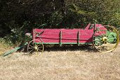 picture of spreader  - antique manure spreader abandoned along the edge of a field - JPG