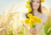 Pretty girl with yellow flowers crown in the grassy sunny summer field holding bouquet