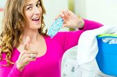 Young woman with laundry basket and detergent in a laundrette she washed their laundry clean and is