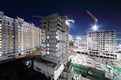 Lit high multi-storey buildings under construction and cranes at dark night.