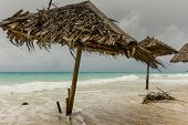 Rough Seas And A Storm Surge Flood A Beach And Sun Shades