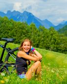 Cheerful female resting on green field after riding on bicycle, Alps mountains background, biking tr