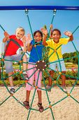 pic of playground  - Cheerful friends climbing the net at a city playground - JPG