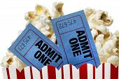 image of matinee  - Close up shot of two movie tickets sticking up out of a tub of popcorn and shot on a white background - JPG