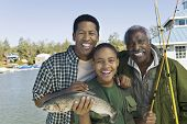 Portrait of happy three generation family with fishing rod and fish at lake