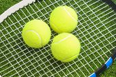 Постер, плакат: Three Tennis Balls Lie On A Tennis Racket Strings Over Green Lawn Surface Tennis Concept