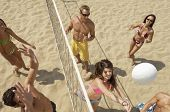 image of volleyball  - High angle view of multiethnic friends playing volleyball on beach - JPG