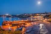 stock photo of moonlit  - Full moon over the harbour and town at Newquay Cornwall England UK - JPG