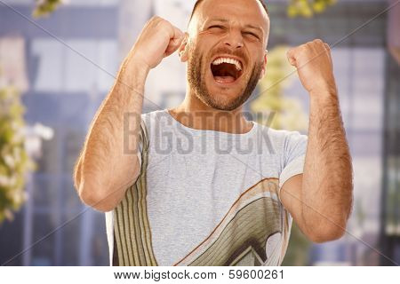 Young man shouting with hapiness outdoors, clenching fists.