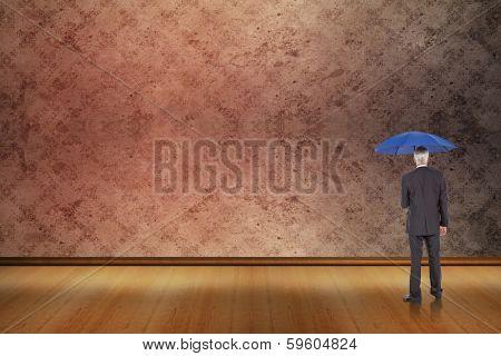 Businessman holding umbrella against grimy room