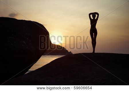 Figure of a girl in contre at sunset on the sea