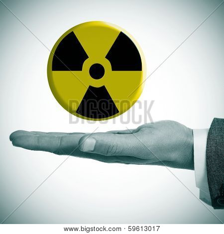 a man hand with a radiation warning symbol in his hand