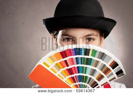 little girl holding a pantone palette on a gray background