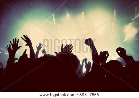 People with hands up having fun on a music concert, disco party. Vintage, retro style