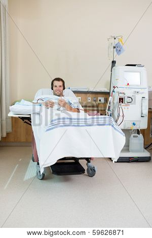 Portrait of smiling male patient listening music while receiving renal dialysis treatment in hospital room