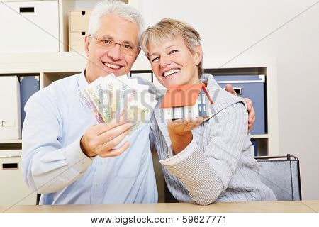 Happy elderly couple with a little house and Euro money in their hands