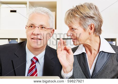 Business woman whispering a secret in a man's ear in the office