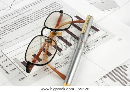 Gläser und Stift auf Finanzdiagramme