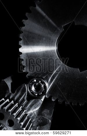 titanium and steel gears and cogwheels set against a black velvet backdrop