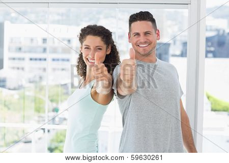 Portrait of fit couple gesturing thumbs up in bright exercise room