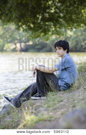 Rapaz adolescente sentado por Lago