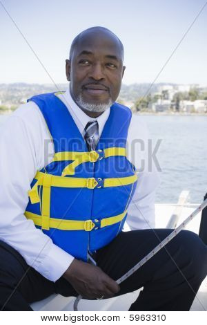 Man In Life Vest On Sailboat